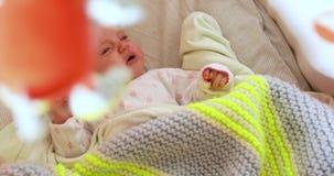 Nyfött behandla som ett barn lägger på baksida i lathunden som gråter arkivfilmer