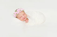 Nyfött behandla som ett barn lindat i den vita blöjan som sovande ler royaltyfria bilder