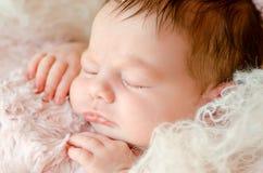 Nyfött behandla som ett barn närbilden som sover på mjuka fluffiga filtar arkivbild