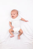 Nyfött behandla som ett barn på det vita arket Fotografering för Bildbyråer