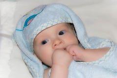 Nyfött behandla som ett barn pojken efter bad i en blå frottéhandduk Arkivbilder
