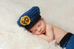 Nyfött behandla som ett barn pojken i polisens hatt Arkivbilder