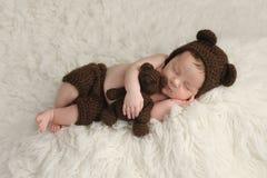 Nyfött behandla som ett barn pojken med den björnhatten och leksaken Arkivfoton