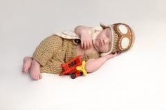 Nyfött behandla som ett barn pojken som bär en flygare Outfit Arkivbild