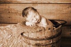 Nyfött behandla som ett barn pojken som sovar i tappningen träbock Fotografering för Bildbyråer