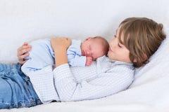 Nyfött behandla som ett barn pojken som sover i armar av hans broder Arkivfoto