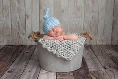 Nyfött behandla som ett barn pojken som sover i en hink royaltyfria foton