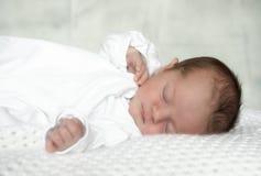 Nyfött behandla som ett barn pojken som sover på den vita filten Royaltyfri Bild