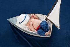 Nyfött behandla som ett barn pojkesjömannen Sleeping i ett fartyg Arkivbild