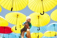 Nyfött behandla som ett barn under färgrika paraplyer Royaltyfri Foto