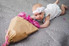 Nyfött behandla som ett barn undersöker världen och att spela med blommabuketten Royaltyfri Foto