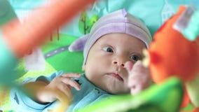 Nyfött ser upp på leksaker stock video