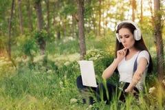 Nyfiken flicka med hörlurar och bärbara datorn Arkivbild