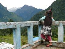 Nyfiken flicka på terrassen som ser till den Marsyangdi dalen Arkivfoto