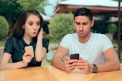 Nyfiken flickvän som kontrollerar meddelanden för texter för pojkväntelefonhäleri fotografering för bildbyråer