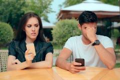 Nyfiken flickvän som kontrollerar meddelanden för texter för pojkväntelefonhäleri arkivfoton