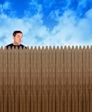 Nyfiken gränsa till man som ser över staketet Arkivbilder