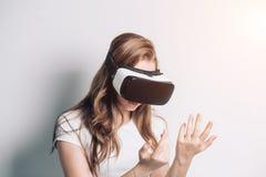 Nyfiken häpen kvinna som försöker ökade verklighetexponeringsglas som känner sig upphetsade om VR-hörlurar med mikrofonsimulering royaltyfri bild