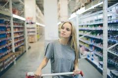 Nyfiken kvinna i supermarket Ung flicka i ett marknadslager med shopping som tänker vad för att köpa Arkivfoto