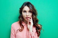 Nyfiken kvinna Ung härlig kvinna i rosa skjorta på blå bakgrund Arkivfoto