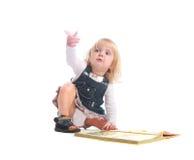 Nyfiken liten flicka som pekar upp hennes finger Arkivfoto