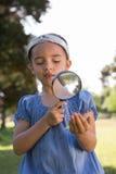 Nyfiken liten flicka som ser bladet Royaltyfri Foto
