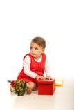 Nyfiken litet barnflicka med gåvan Arkivfoton