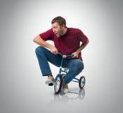 Nyfiken man på barns cykel arkivfoto