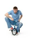 Nyfiken man på barns cykel på vit royaltyfria bilder