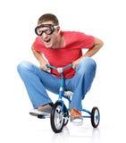 Nyfiken man på barns cykel, på white Arkivfoton