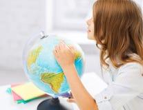 Nyfiken studentflicka med jordklotet på skolan Arkivbild