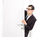 Nyfiken ung affärsman som ser till och med en dörr royaltyfri fotografi