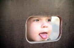 Nyfiken unge som spionerar till och med hålet i träväggen på lekplats Royaltyfri Foto