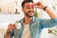 Nyfiket och le tillfälligt kaffe för drinkar för manfixandesolglasögon arkivfoto
