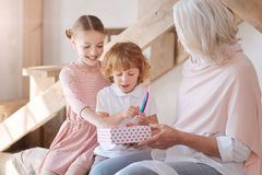 Nyfikna lyckliga barn som ser deras gåvor Fotografering för Bildbyråer