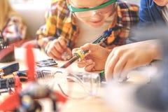 Nyfikna pojkar som arbetar med instrumentet Royaltyfri Fotografi