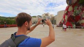 Nyfikna turister som fotograferar sikt av samtida konst på telefonkamera arkivfilmer