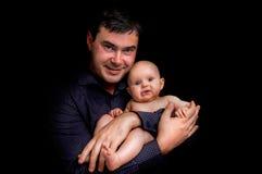 Nyfött behandla som ett barn att ligga på father&en x27; s-händer som isoleras på svart Royaltyfri Foto