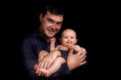Nyfött behandla som ett barn att ligga på father&en x27; s-händer som isoleras på svart Arkivbild