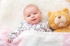 Nyfött behandla som ett barn flickan på hennes filt med hennes nallebjörn Fotografering för Bildbyråer