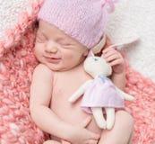Nyfött behandla som ett barn flickan som sover med en leksakhare Arkivfoton