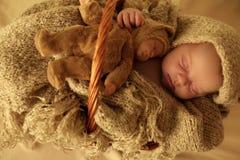 Nyfött behandla som ett barn flickan som sover under den hemtrevliga filten i korg Arkivfoto