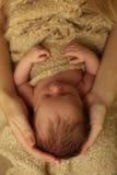 Nyfött behandla som ett barn flickan som sover under den hemtrevliga filten i mammans händer Royaltyfri Foto