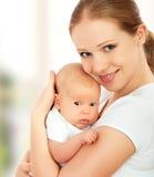 Nyfött behandla som ett barn i armarna av modern Arkivbilder
