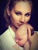 Nyfött behandla som ett barn i armarna av modern Arkivfoto