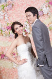 Nygift personbrud och brudgum som poserar med blommagarneringen i backgr Royaltyfri Fotografi