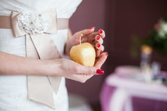 Nygift personhand med det guld- äpplet Arkivfoto