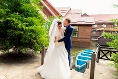 Nygift personpar, brudgum och brud som har roligt utomhus Royaltyfri Fotografi