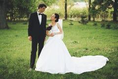 Nygift personpar i trädgård royaltyfri bild