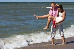 Nygift personpar på strand Royaltyfria Bilder